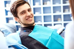 man sitting in dentist chair smiling
