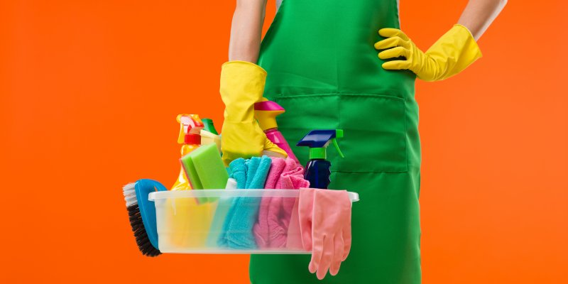 woman holding bucket of cleaning products