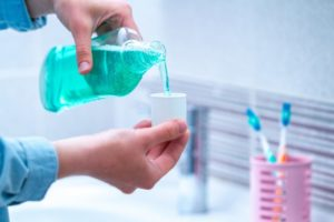 person pouring antibacterial mouthwash