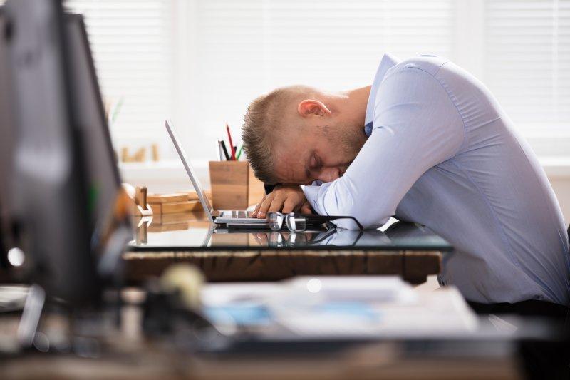 A man sleeping at his desk.
