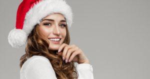 Woman wearing a Santa hat after teeth whitening.